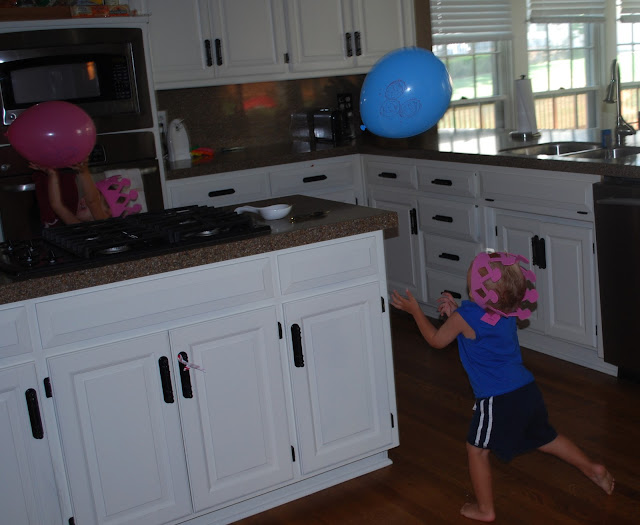 toddler batting baloons around