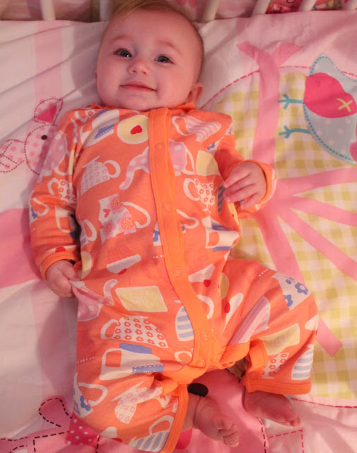 smiling baby girl wearing orange footless all in one with biscuits, cakes, teacups and teapots pattern