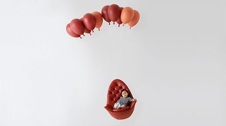 Silla suspendida por globos parece estar flotando en el aire