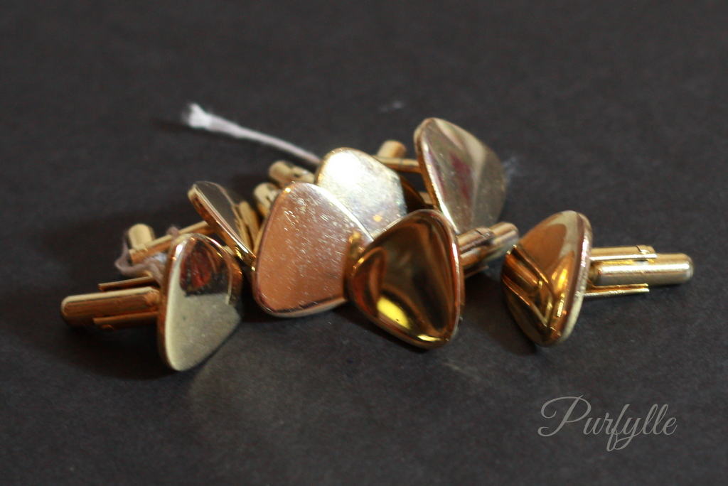 brass cuff links piled together