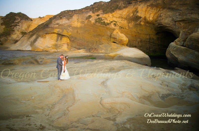 wedding couple standing on sandstone of Cape Kiwanda