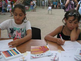 Két ötödikes lányka old szövegértéses játszólapokat. Színes ceruza, lapok, Törpmanó játszófüzete, lehúzósképek hevernek előttük az asztalon..