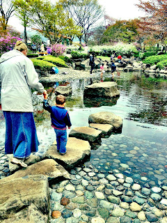 mom and child walking stone path in tadpole pond in Japan