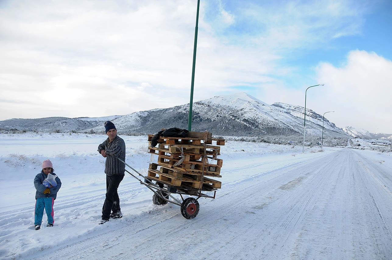 Un hombre acarrea leña en el Alto de San Carlos de Bariloche