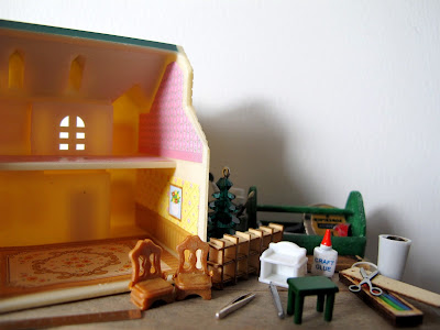 Close up of a modern doll's house miniature scene of a workbench with a dolls' house on top, surrounded by tools, paint and miniature furniture.