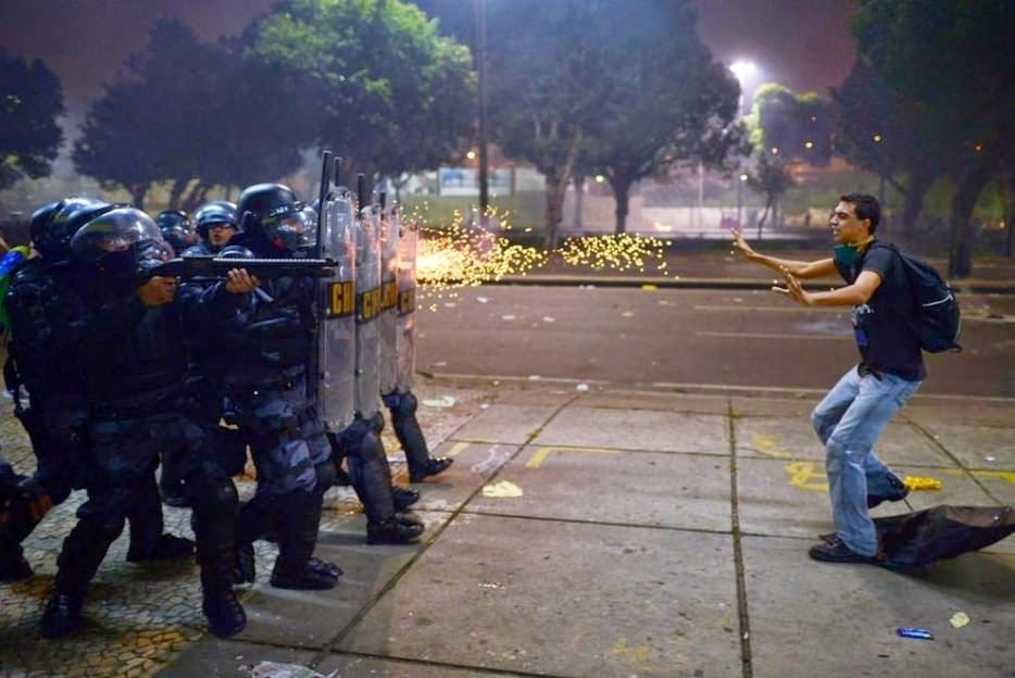 A Brazilian protester stands before gunfire during protests against corruption and police brutality. - The 63 Most Powerful Photos Ever Taken That Perfectly Capture The Human Experience