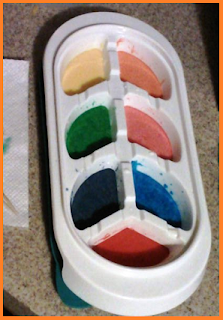 Frozen baby food tray holding yellow, orange, green, pink, purple, blue, and red water colors.