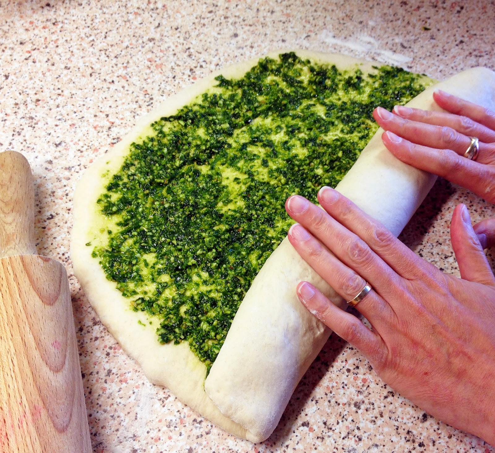 rolling dough to make pesto swirl bread