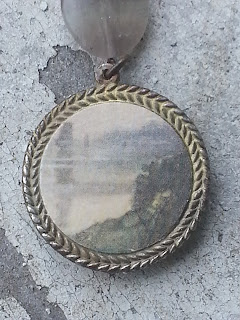 the back of the pendant with vintage ephemera