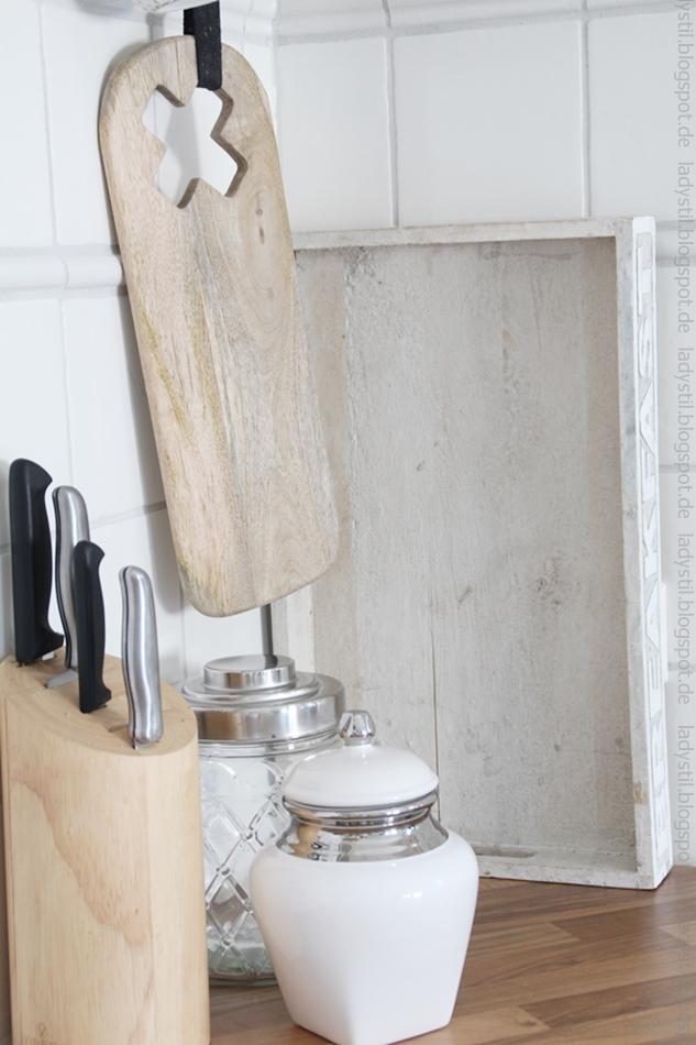 Messerblock in Holz daneben weiß/silberne Dose darüber hängt ein Schneidbrett aus Holz