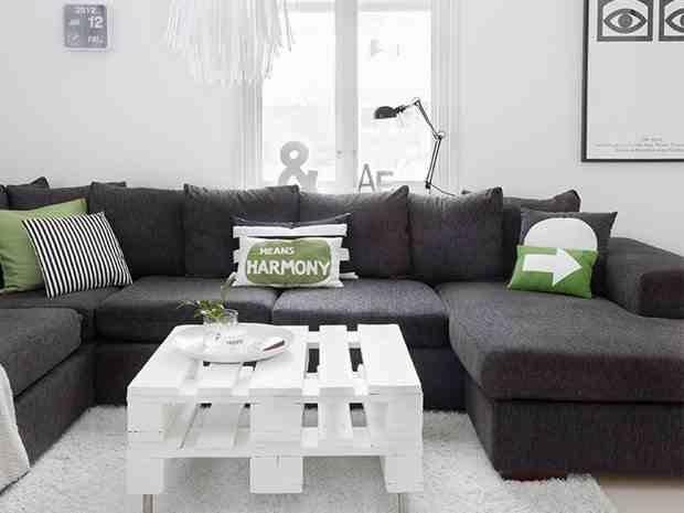 Monochromatyczna aranżacja, biały stolik  zpalet, poduszki z napisami, typografia