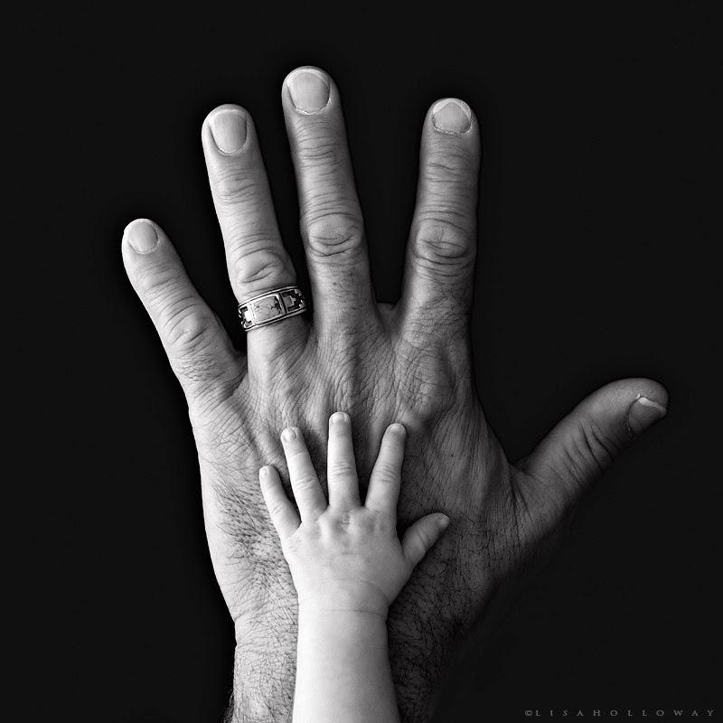 photo de Lisa Holloway représentant une main d'enfant posée sur une main d'homme en noir et blanc