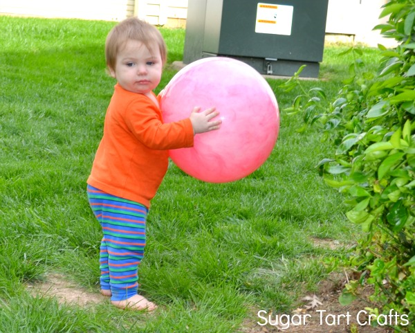 Toddler boy carrying a large pink ball