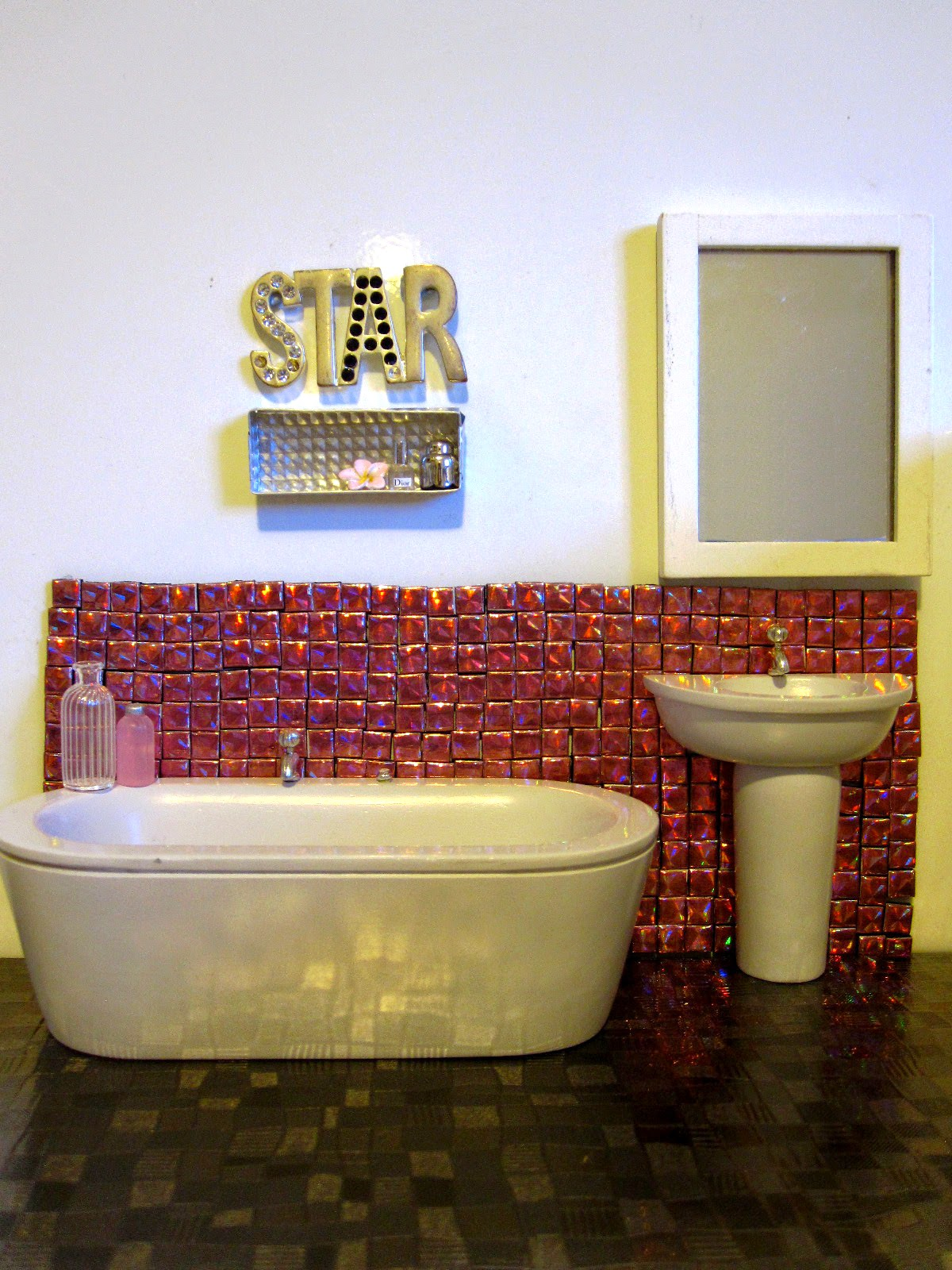 Modern dolls house miniature bathroom with pink sparkly tiles on the wall and grey shiny 'stone' floor.