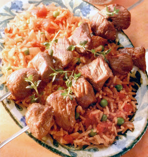 Lamb kebabs on metal skewers served on a bed of tomato rice with peas