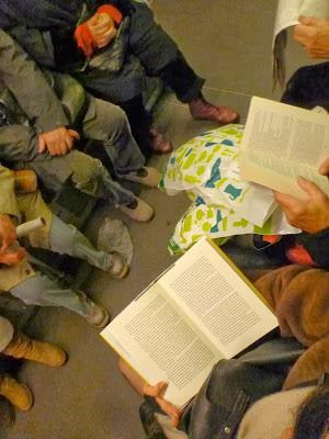 Draufsicht: Zwei Buch- und ein Zeitungsleser in der Reihe. Die gegenüberliegende Seite liest nicht.