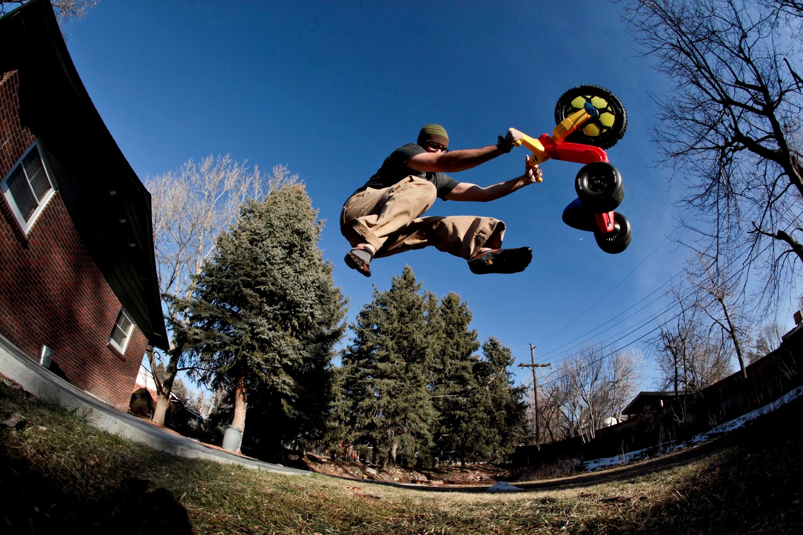 A dad making a big jump on his sons' Big Wheel in the backyard.