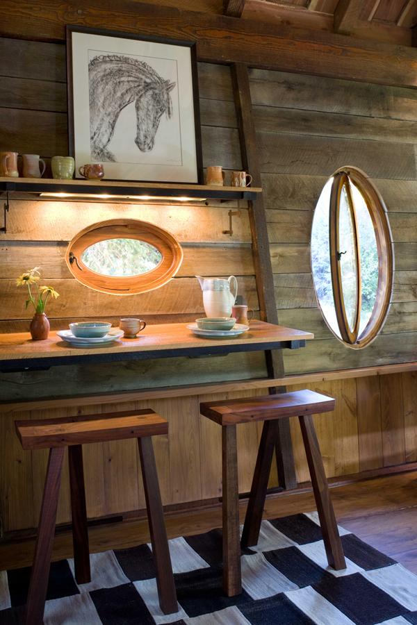 mesa con dos taburetes rusticos y ventana obalada