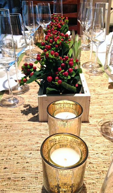 DIY centerpiece with winter berries and gold votive candles