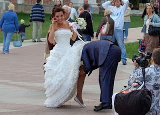 funniest wedding picture: the bridegroom puts his head under the wedding dress