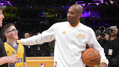 Los Angeles Lakers forward Kobe Bryant talks with Make-A-Wish recipient Yitzi Tiechman before a game against the Charlotte Hornets on Sunday at Staples Center. The Lakers signed the teenager to a one-day contract before the game.