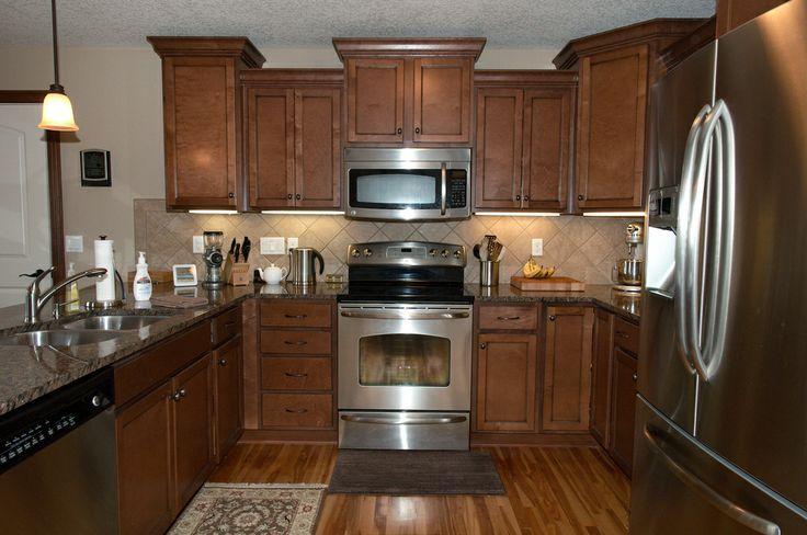 Warm Medium Brown Cabinets With Baltic Granite Countertops