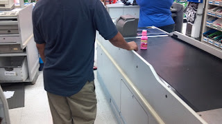 person in checkout line with pepto bismol