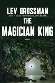 Cover art for The Magician King, featuring an eclipse of the sun visible through a natural stone arch on the shore of what appears to be a vast sea. Most of the cover is cast into shadow by the dark, weather-worn stone, but the sea and sky surrounding the eclipse are a bright grey.