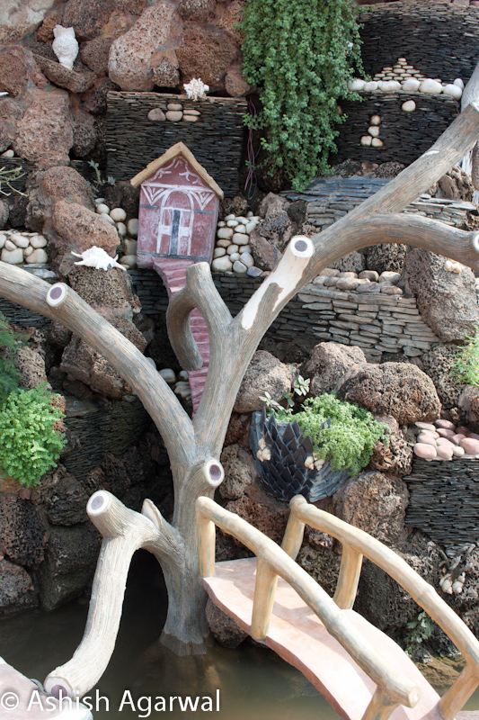 Close up of a small bridge, tree, and doll house as part of an attraction