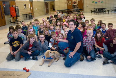 A large group of second grade children sit on a tile floor in a group behind the golden retriever puppy and his raiser. The raiser is dressed in blue and is kneeling with his leash in her right hand. The puppy is looking at her. There is a red Kong toy on the floor in front of the puppy and a light brown mat. In the background are lunch tables.