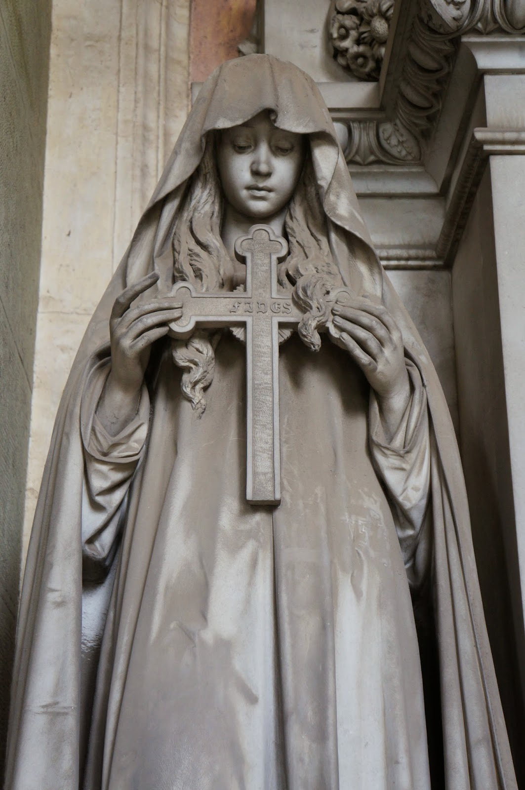 Beautiful stone statuary in the Staglieno Cemetery in Genoa Italy - beautiful girl with cross