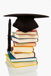 A mortarboard sits on top of a stack of books.