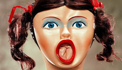 Face of a blowup doll, a woman with pig tails, blue eye makeup and a bright red mouth open wide.