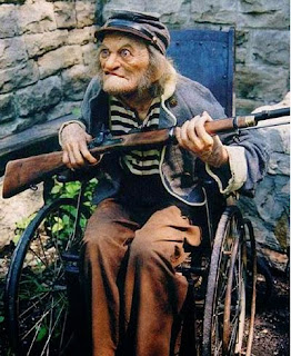 old man in wheelchair with gun