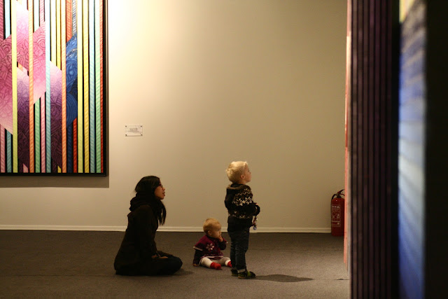 Ping, Anton and Neve looking at a painting by Ahmet Güneştekin.