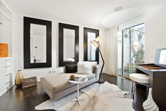 Office in a Soho Condo in New York City with white walls, black mirrors and an animal skin rug