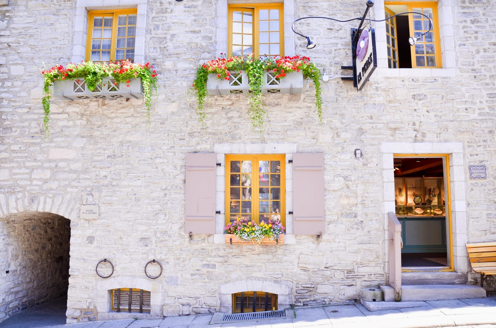 Beautiful flower baskets and yellow trip on doors and windows in Old Quebec, Quebec City