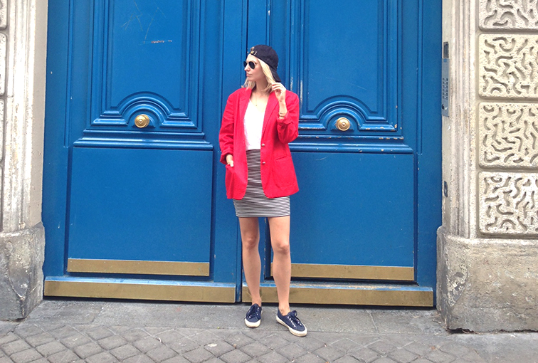 Giant blue doors in Paris, red blazer, striped mini skirt, backwards cap, navy Supergas