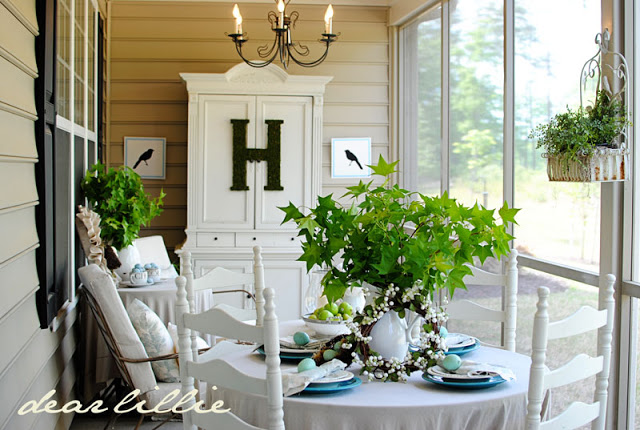 This screen in porch is a quaint little escape with white furniture and a french style hutch