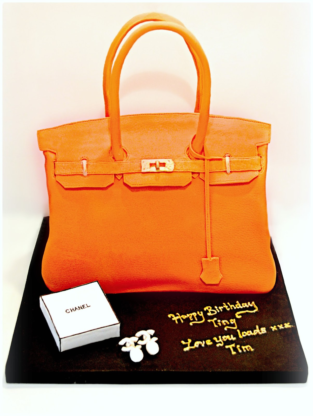 Cherie Kelly's Orange Hermès Birkin Handbag Cake with a pair of Chanel Pearl Earrings