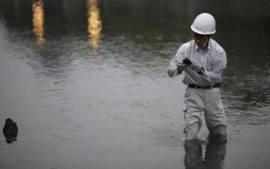 Ông Kayo nhặt một mảnh vỡ của Mái vòm Genbaku dưới sông Motoyasu