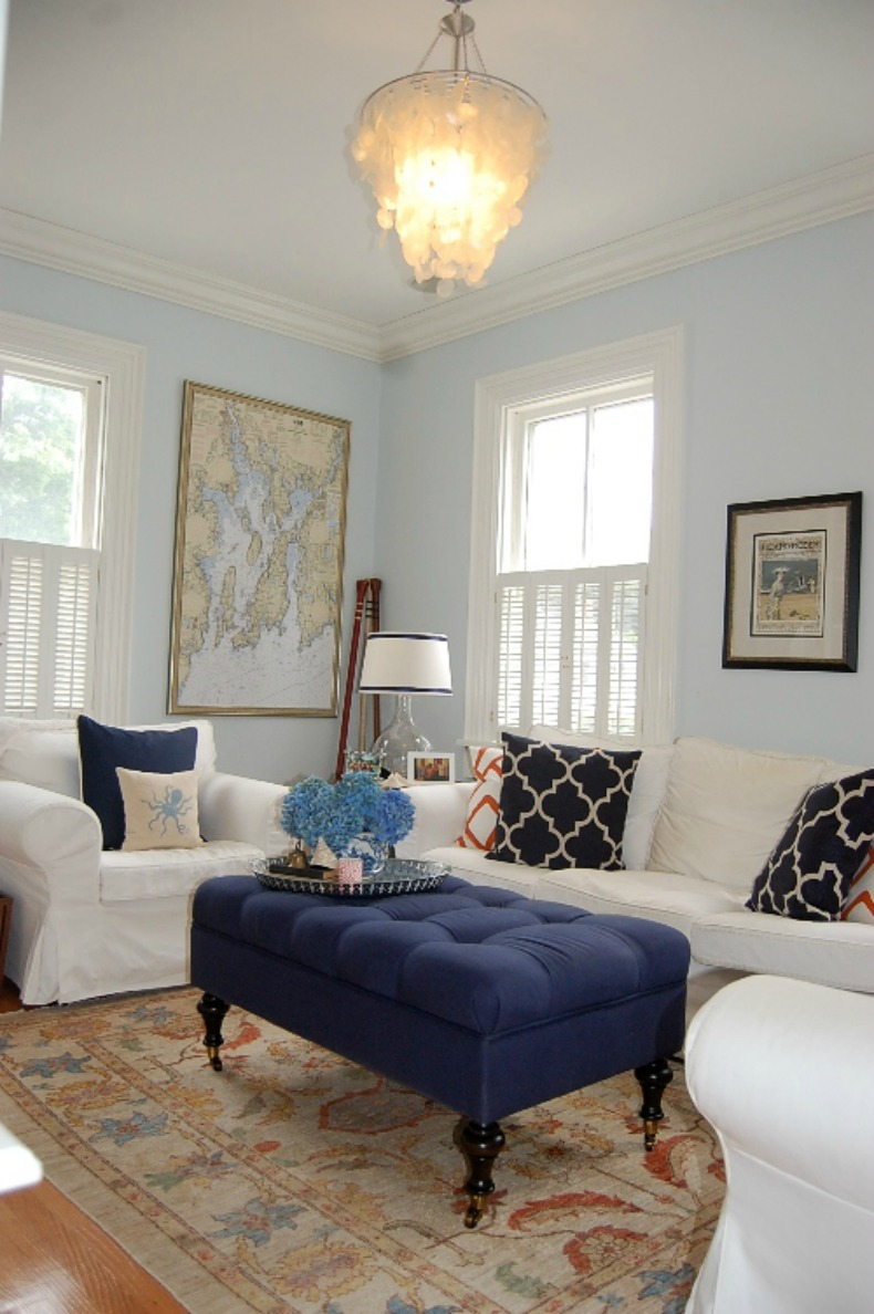 Coastal living room with shell chandelier, white slipcover sofa and chairs