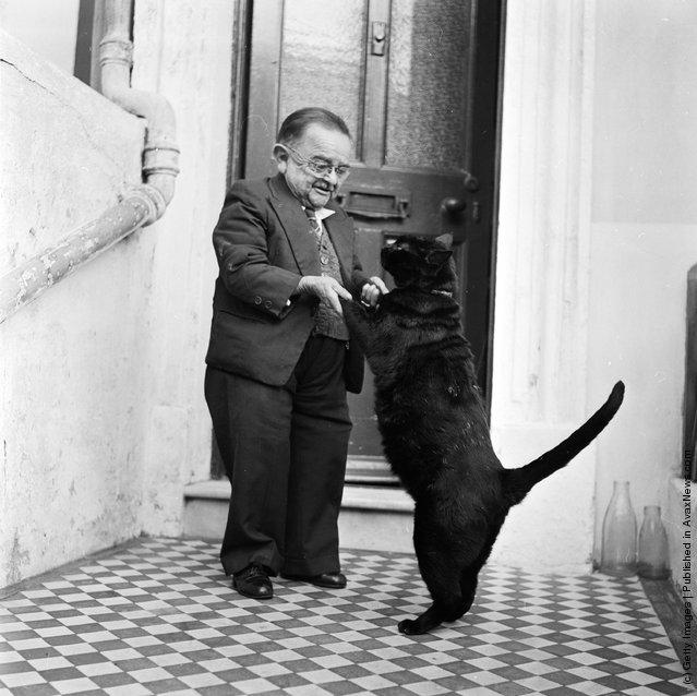 Генри Беренс (Henry Behrens), самый маленький человек в мире танцует со своей домашней кошкой в дверном проеме своего дома.