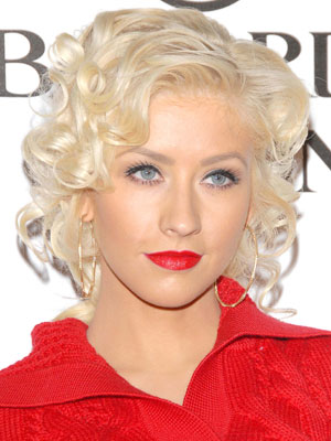 Delicate coils add a romantic touch to Christina Aguilera's thoroughly feminine, swept-back hairstyle.