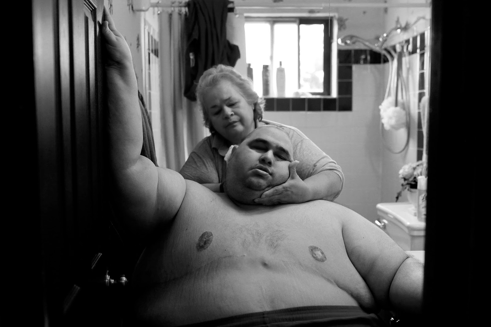 Copyright: ©Lisa Krantz, United States, Shortlisted, Contemporary Issues, Professional, 2015 Sony World Photography Awards. Image Name: A Life Apart: The Toll of Obesity. Image Description: At almost 600 pounds, Hector Garcia Jr. finds simple daily tasks like bathing a challenge. He struggled to walk across the hall from his bedroom to the bathroom so that his mother, Elena, could wash him after having cut his hair in November 2010. A month before, Hector started dieting after he realized he was close to his highest known weight, 636 pounds.