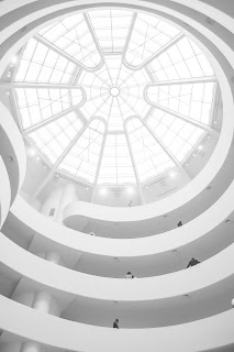 several stories in a round building with large circular skylight at top; all white image
