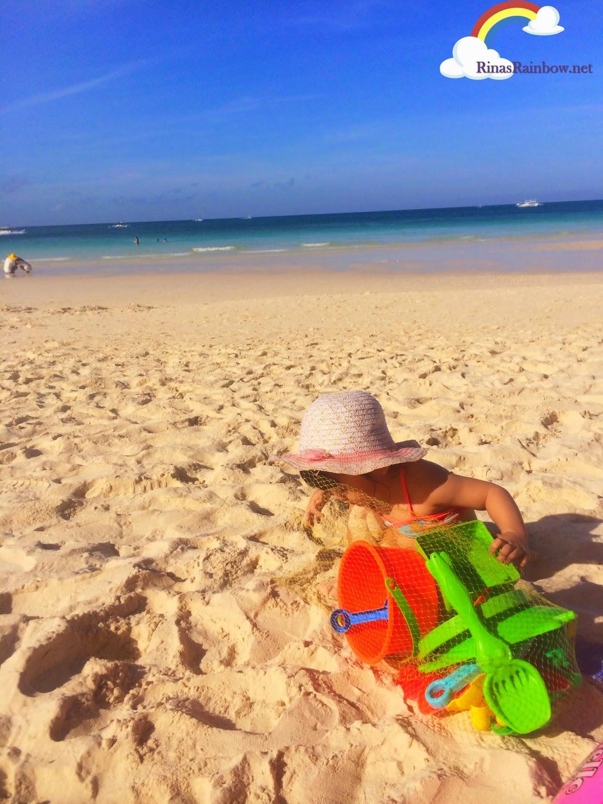 toddler playing in beach