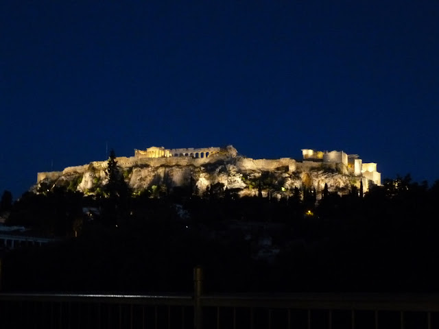 A view of the ruins of Acropolis lit up against a dark blue sky
