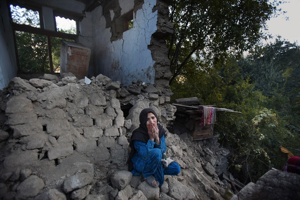 70 Of The Most Touching Photos Taken In 2015 - A Pakistani woman, who lost two grandsons in Monday's earthquake, mourns as she sits in the rubble of her home. More than 380 people were killed in the region.