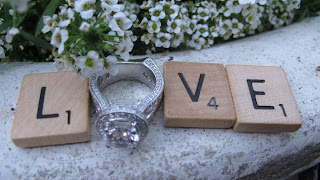 the word love in scrabble pieces with ring for the O